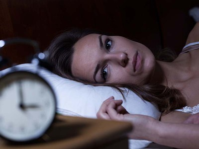 Neurofeedback Insomnia: A woman laying awake because she either can't fall asleep or stay asleep, but Neurofeedback may help!
